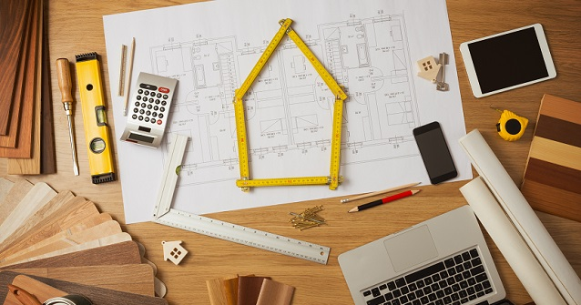 Architect and home interior decorator desktop with tools laptop wood swatches and home project draft top view a meter is composing a house at center